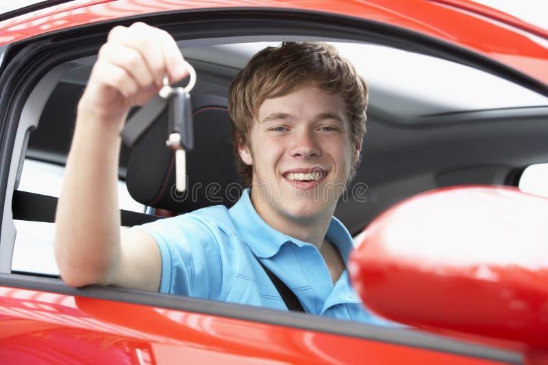 Adolescente que senta-se em chaves do carro da terra arrendada do carro fotos de stock royalty free