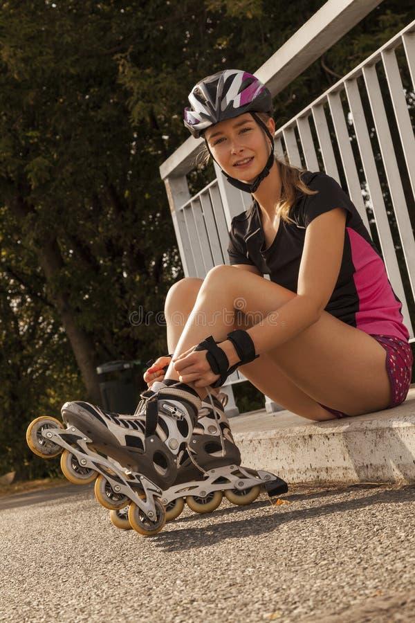 Adolescente que senta-se em um freio que ata acima de seus patins de rolo fotografia de stock royalty free