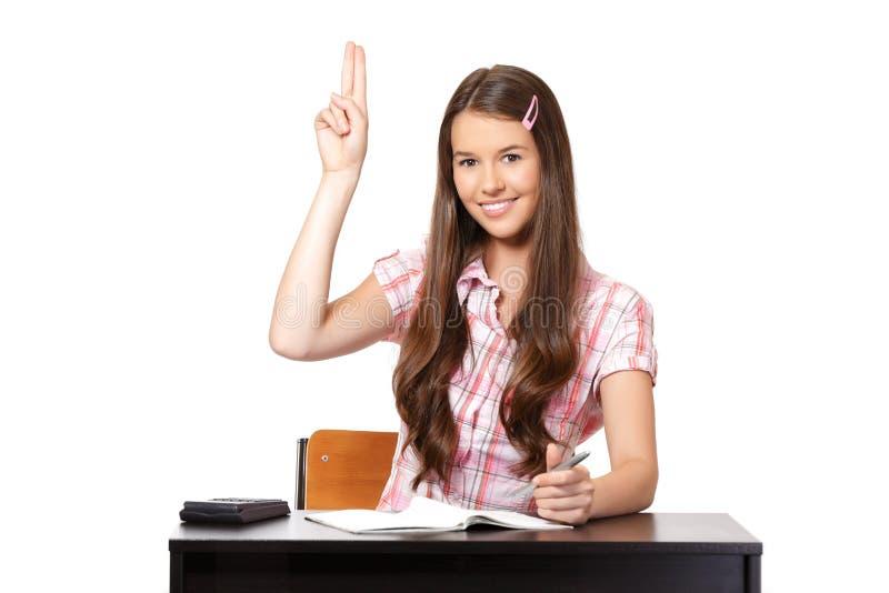 Adolescente que senta-se na sala de aula com raisedhand foto de stock royalty free