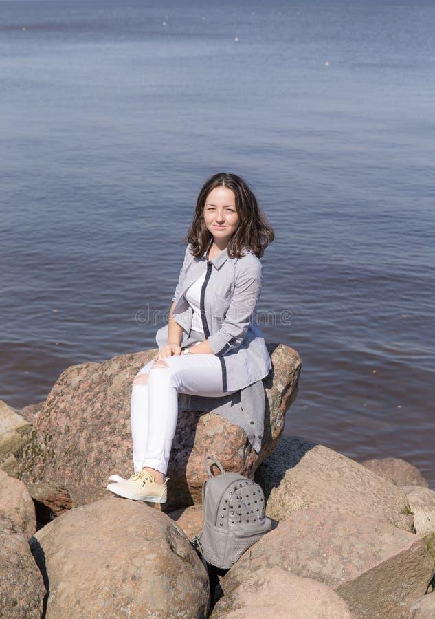 Adolescente que senta-se nas rochas imagem de stock royalty free