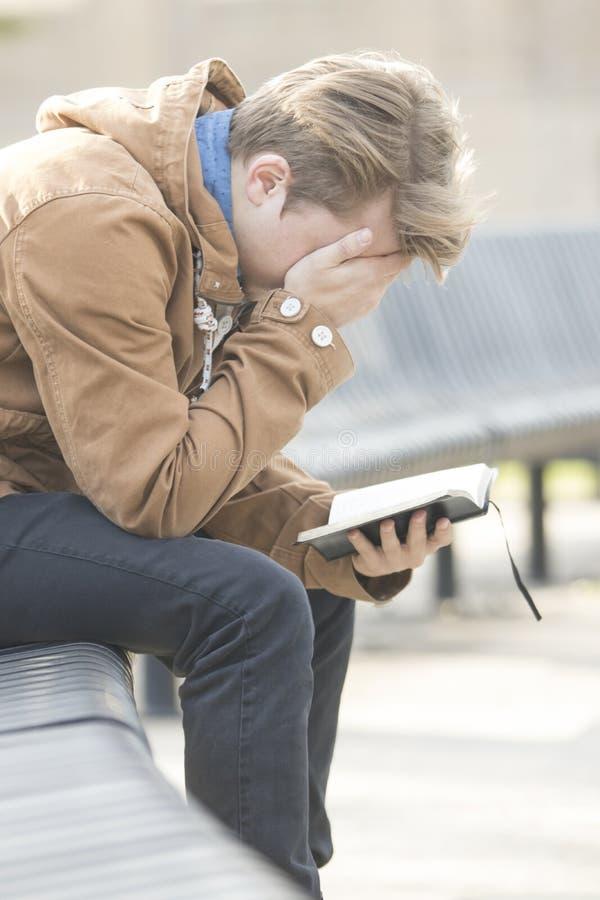 Adolescente que senta-se no banco e em rezar imagens de stock royalty free
