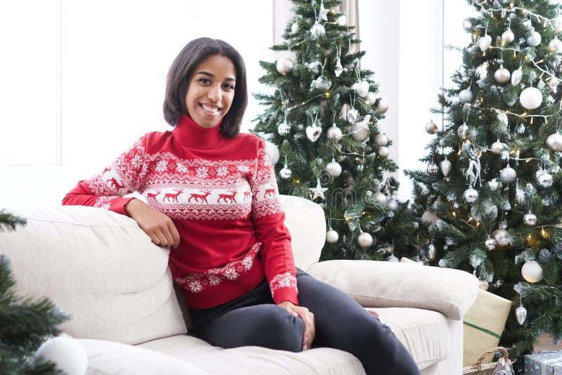 Adolescente que senta-se no sofá ao lado da árvore de Natal foto de stock