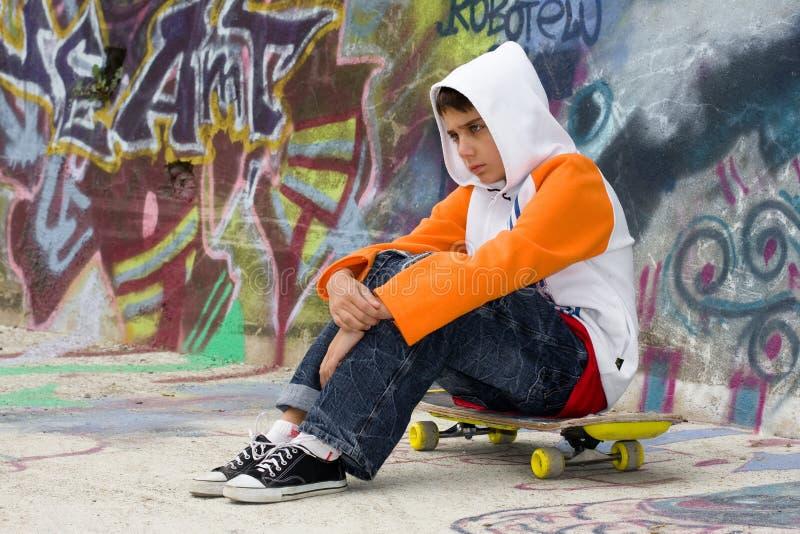 Adolescente que senta-se perto de uma parede dos grafittis fotografia de stock royalty free