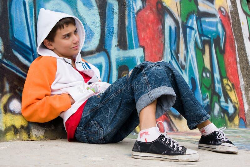Adolescente que senta-se perto de uma parede dos grafittis imagem de stock