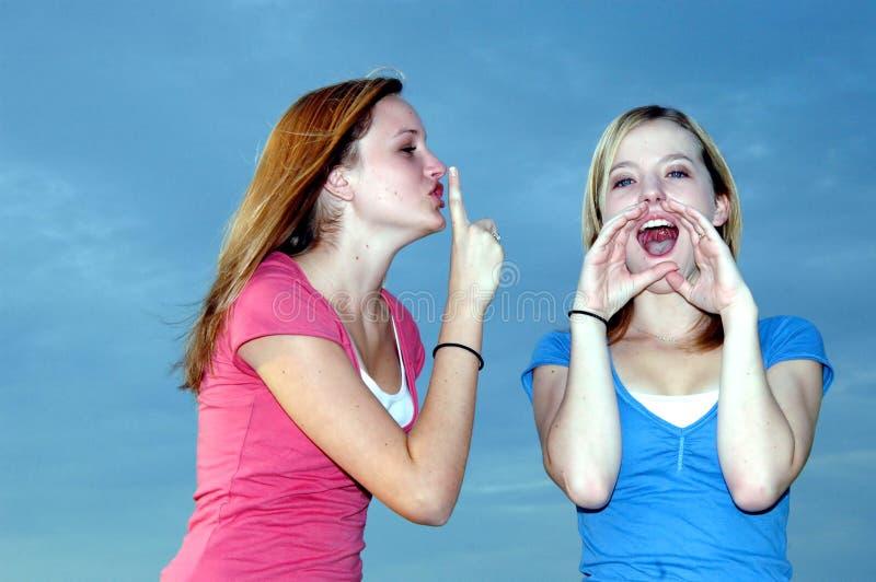 Adolescente que shushing o amigo alto imagem de stock royalty free