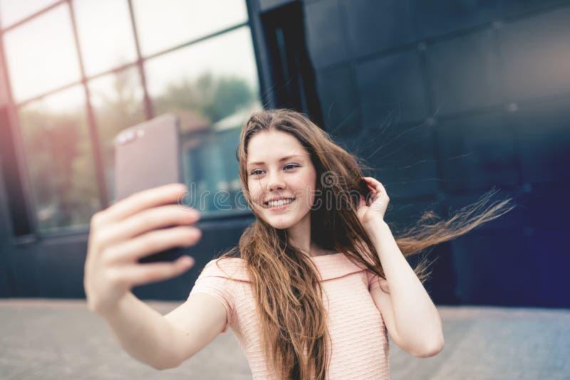 Adolescente que sorri ao tomar um selfie foto de stock