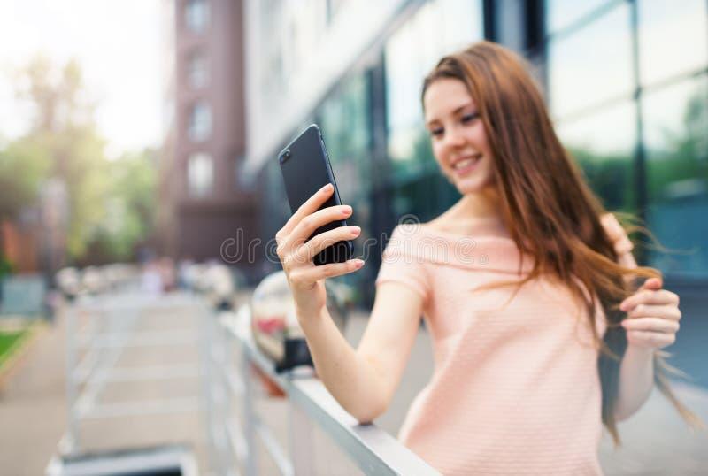Adolescente que sorri ao tomar um tiro do selfie fotografia de stock royalty free