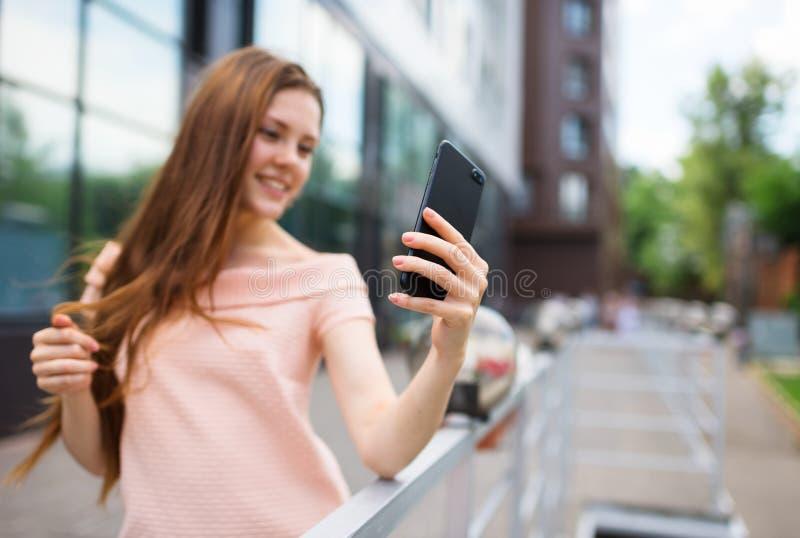 Adolescente que sorri ao tomar um tiro do selfie imagens de stock