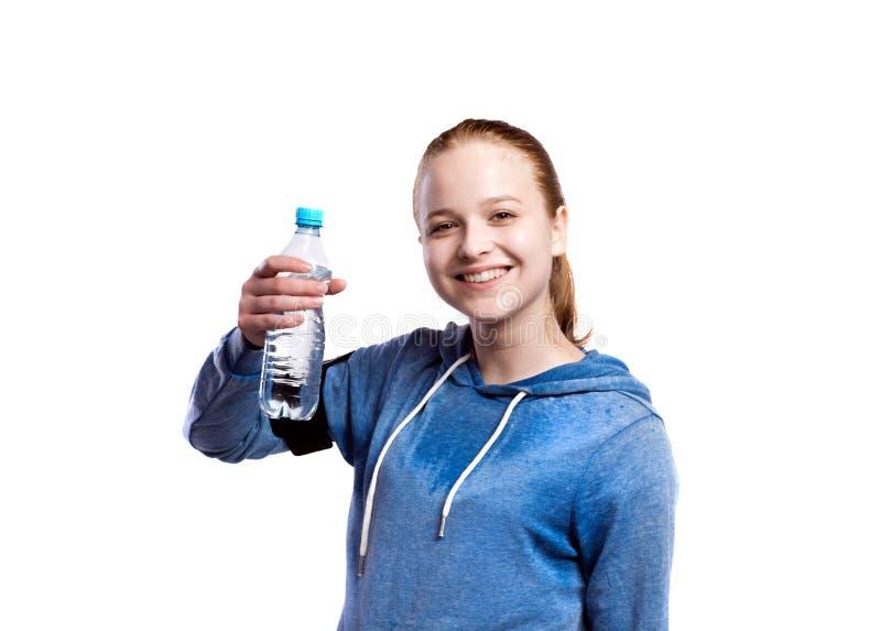 Adolescente que sostiene la botella de agua Tiro del estudio, aislado fotografía de archivo libre de regalías