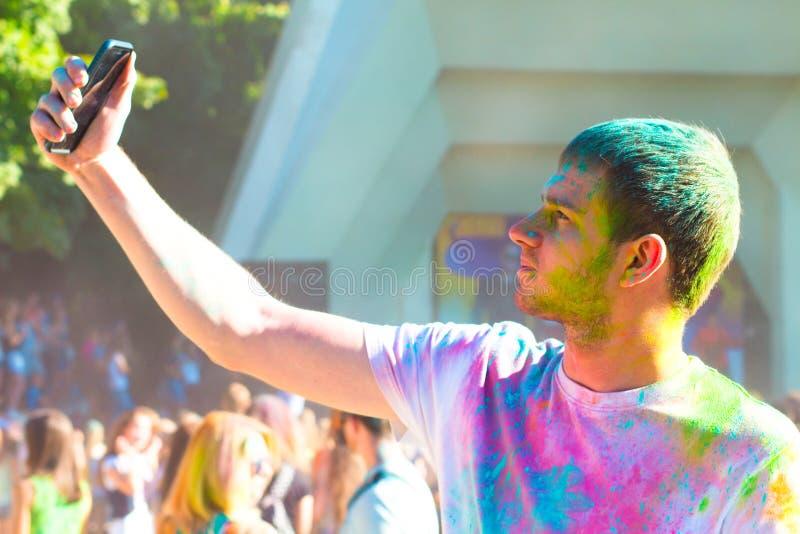Adolescente que toma la foto en el teléfono móvil en festival del color del holi foto de archivo