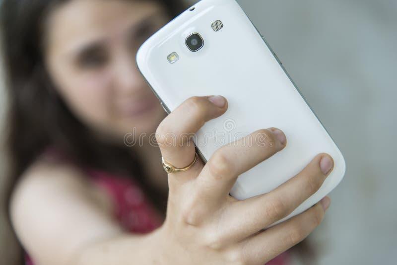 Adolescente que toma um selfie com seu telefone imagem de stock