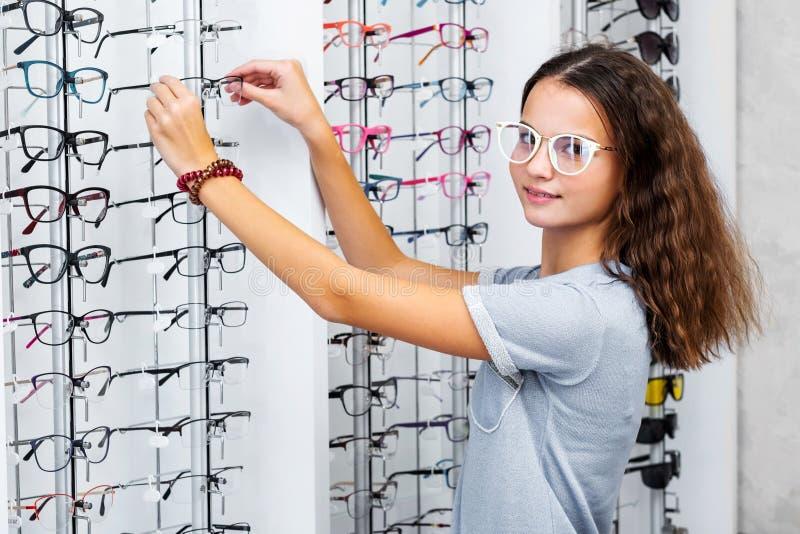 Adolescente que toma vidros pretos da mostra na loja ótica fotografia de stock
