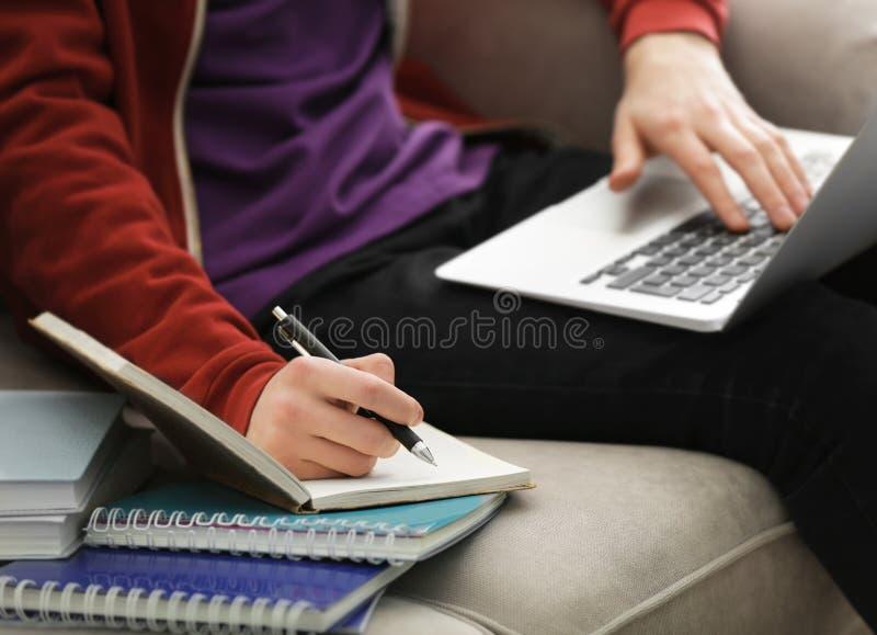 Adolescente que trabalha com portátil ao fazer lições imagens de stock