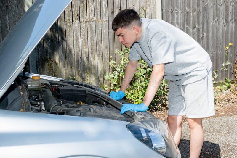 Adolescente que trabalha em um carro imagens de stock