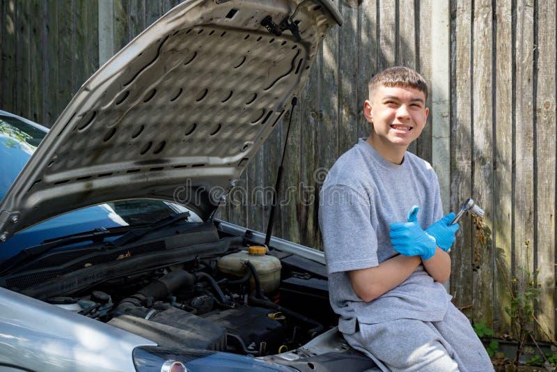 Adolescente que trabalha em um carro fotos de stock royalty free