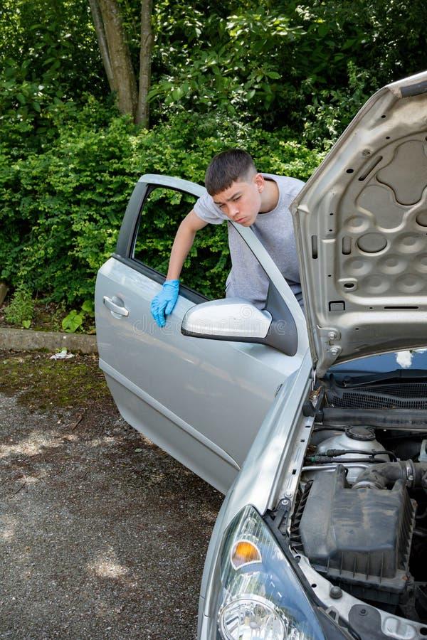 Adolescente que trabalha em um carro imagem de stock