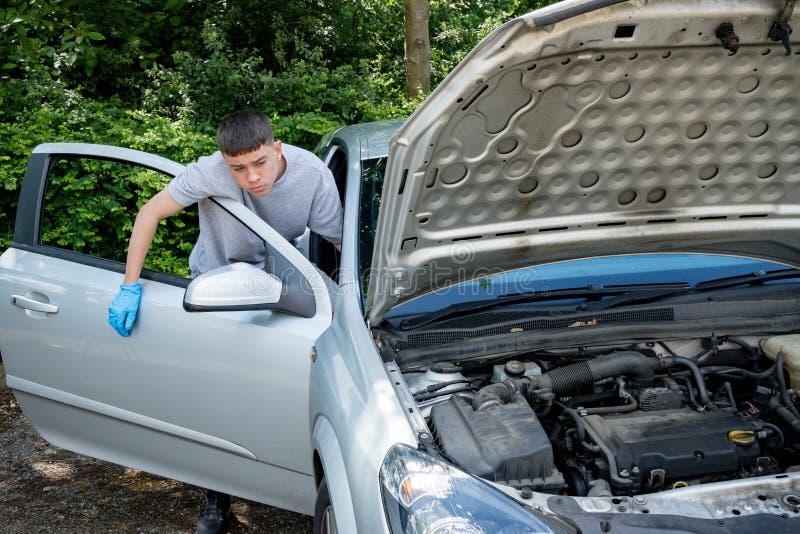 Adolescente que trabalha em um carro imagem de stock royalty free