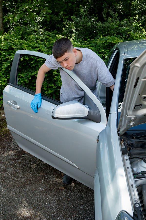 Adolescente que trabalha em um carro fotografia de stock royalty free