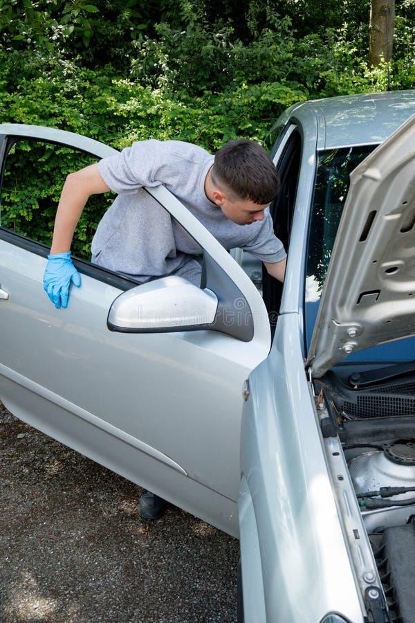 Adolescente que trabalha em um carro foto de stock royalty free