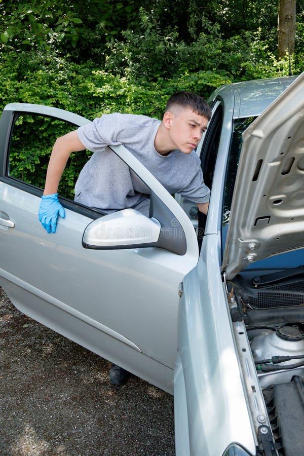 Adolescente que trabalha em um carro imagens de stock royalty free