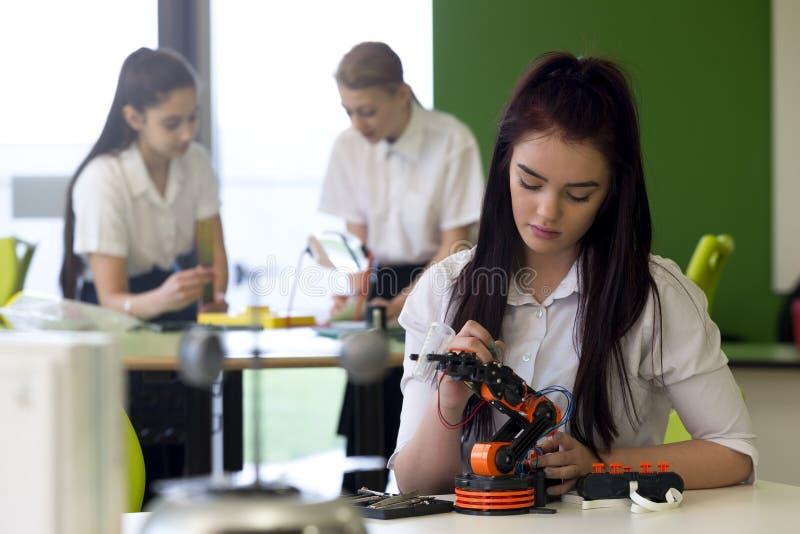 Adolescente que trabalha no braço robótico imagens de stock royalty free