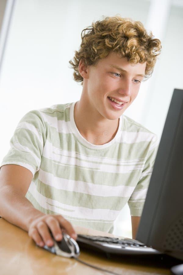 Adolescente que usa o computador de secretária fotografia de stock royalty free