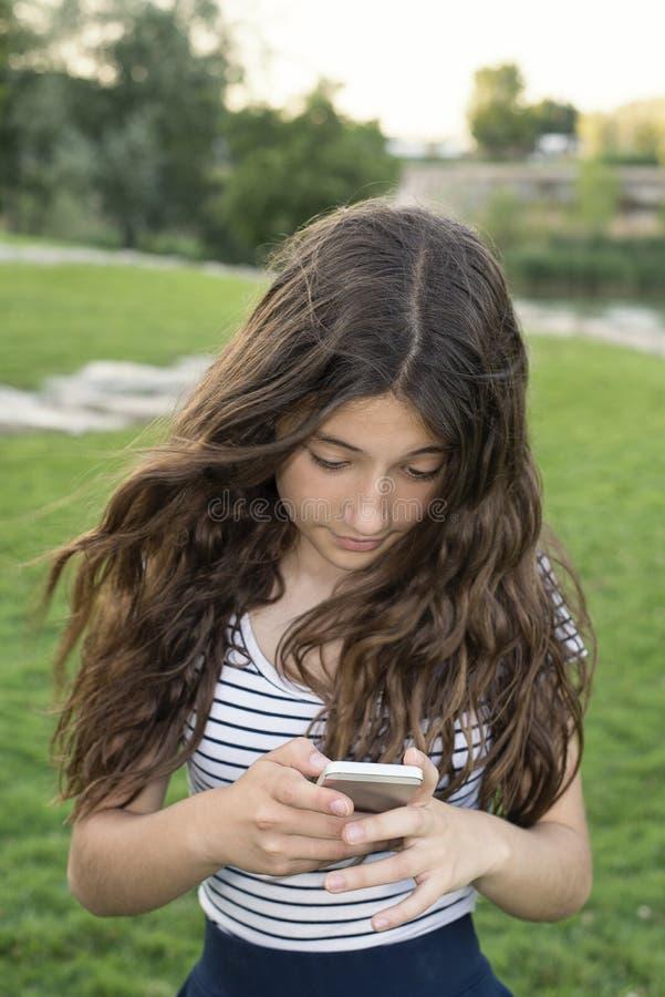 Adolescente que usa o móbil em um parque fotos de stock royalty free