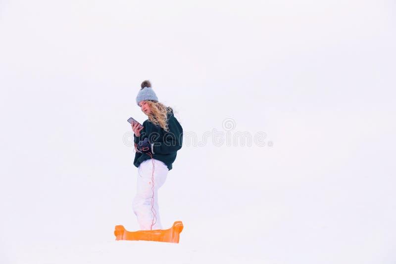 Download Adolescente Que Verifica Seu Telefone Celular Durante O Divertimento Exterior Do Inverno Imagem de Stock - Imagem de caucasiano, longo: 107529125