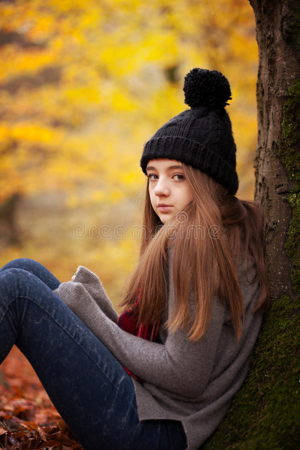 Adolescente que veste um chapéu de lã que senta-se ao lado de uma árvore fotos de stock royalty free