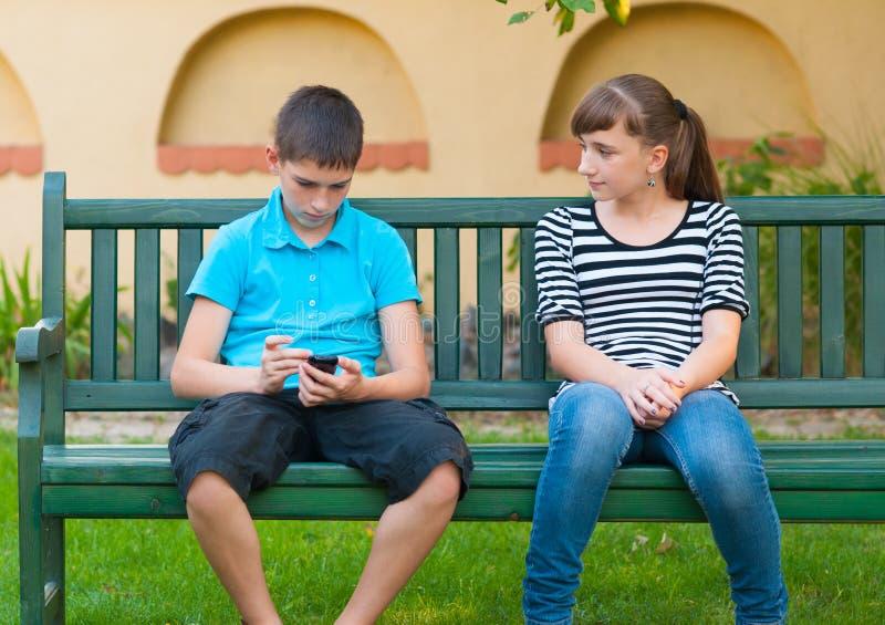 Adolescente regardant avec amour le garçon indifférent photo stock
