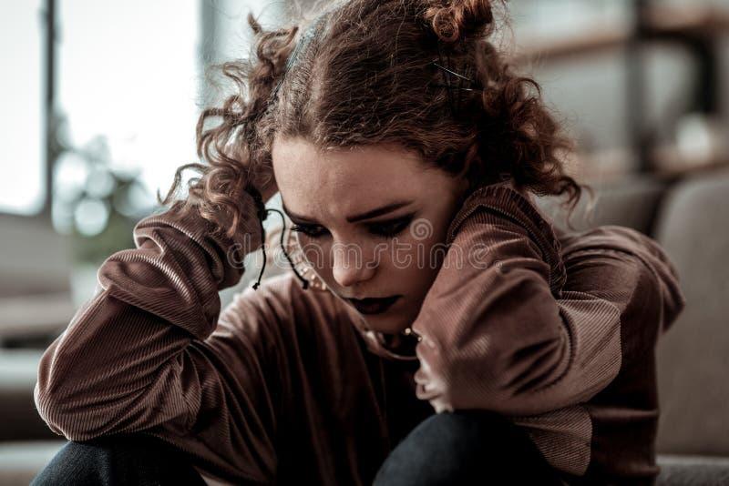 Adolescente rizado con malo oscuro de la sensación del maquillaje después del divorcio de padres imagen de archivo libre de regalías