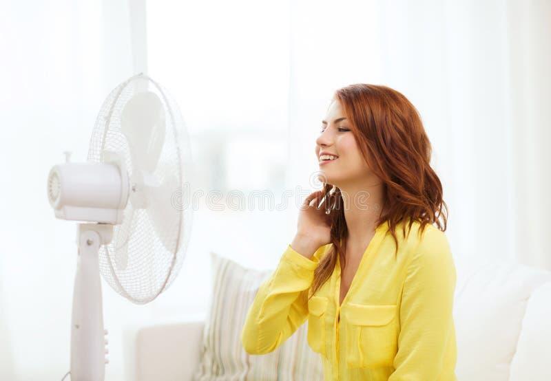 Adolescente rousse de sourire avec la grande fan à la maison image libre de droits