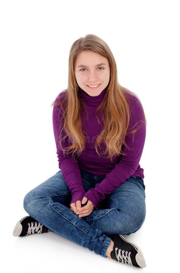 Adolescente rubio adorable que mira la cámara que se sienta en piso foto de archivo