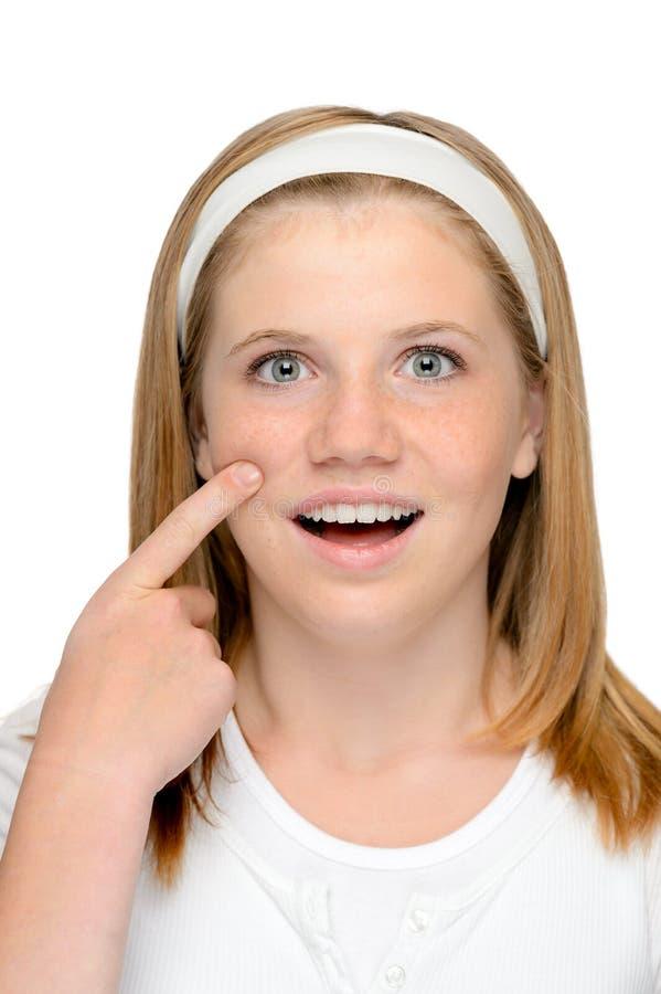 Adolescente rubio joven que mira que muestra cuidado de piel foto de archivo libre de regalías