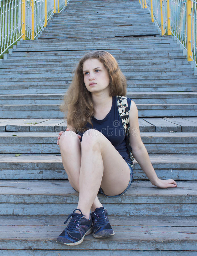 Adolescente só da menina que senta-se em escadas foto de stock