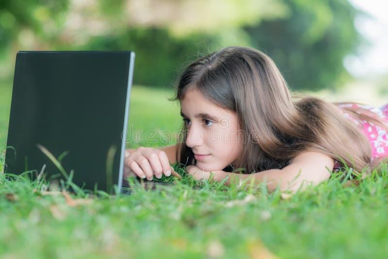 Adolescente s'étendant dans l'herbe et à l'aide de son ordinateur portable photos stock