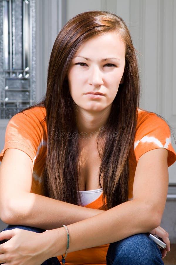 Adolescente s'asseyant à l'extérieur photo libre de droits