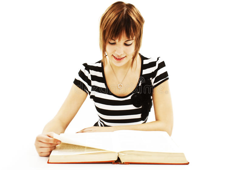 Adolescente s'asseyant au bureau et au livre de relevé photo libre de droits