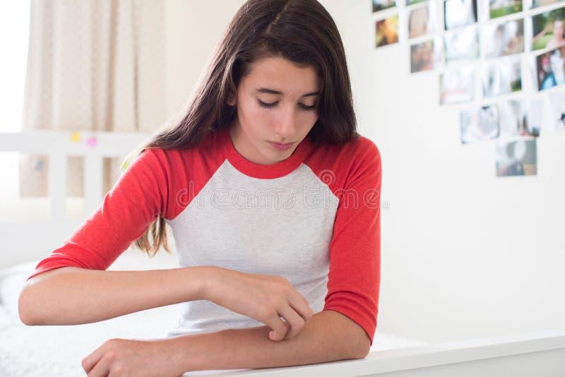 Adolescente s'asseyant dans la chambre à coucher rayant le bras photos libres de droits