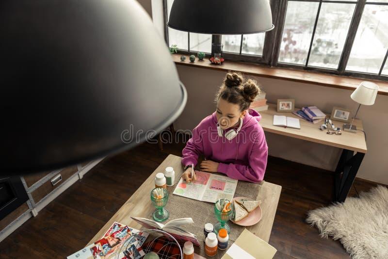 Adolescente s'asseyant dans la cuisine et écrivant la composition photo libre de droits