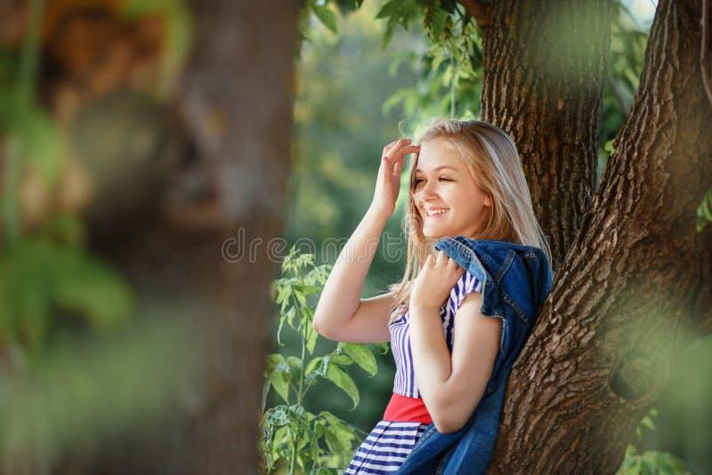Adolescente s'asseyant sur l'arbre en été image stock