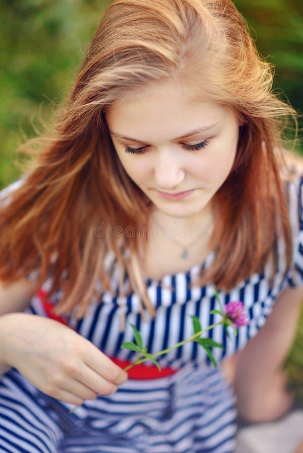 Adolescente s'asseyant sur l'herbe en été photographie stock