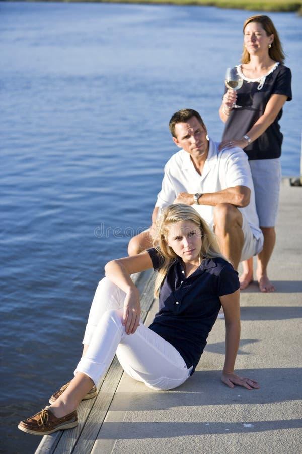 Adolescente s'asseyant sur le dock par l'eau avec des parents image stock