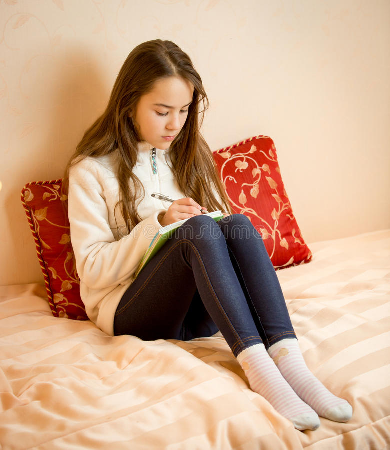 Adolescente s'asseyant sur le lit et écrivant des poèmes en journal intime photo libre de droits