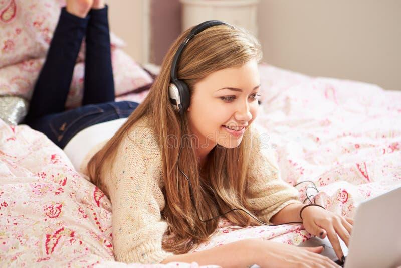Adolescente se trouvant sur le lit utilisant les écouteurs de port d'ordinateur portable photos stock