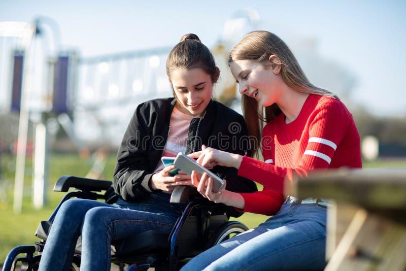 Adolescente in sedia a rotelle che esamina telefono cellulare con l'amico in parco immagini stock