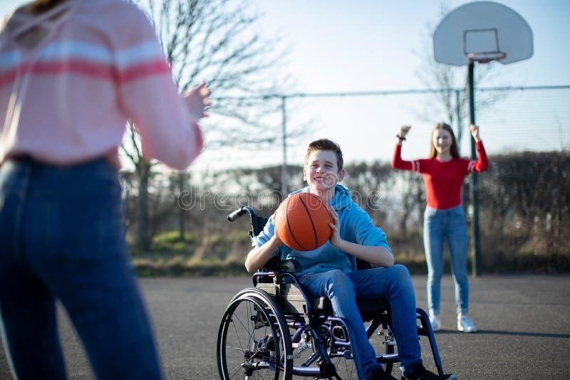 Adolescente in sedia a rotelle che gioca pallacanestro con gli amici immagini stock libere da diritti