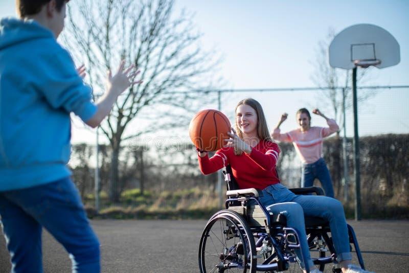 Adolescente in sedia a rotelle che gioca pallacanestro con gli amici fotografia stock