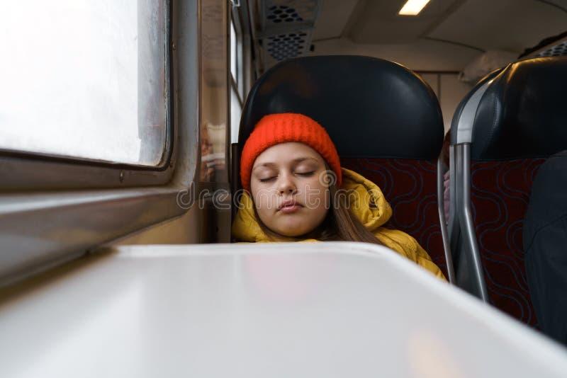 Adolescente sentada en un tren suburbano y resbalando imágenes de archivo libres de regalías