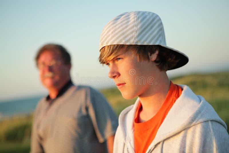 Adolescente serio con el padre foto de archivo